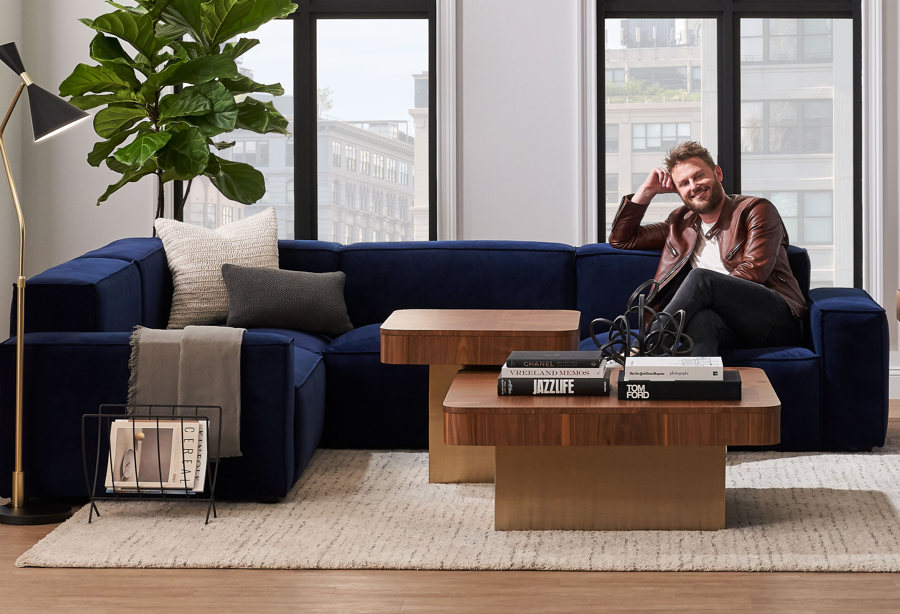 bobby berk sitting on furniture in a modern setting