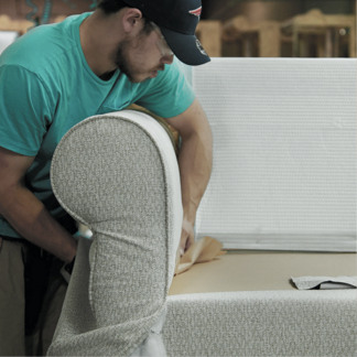Photo of a man putting upholstery on a couch